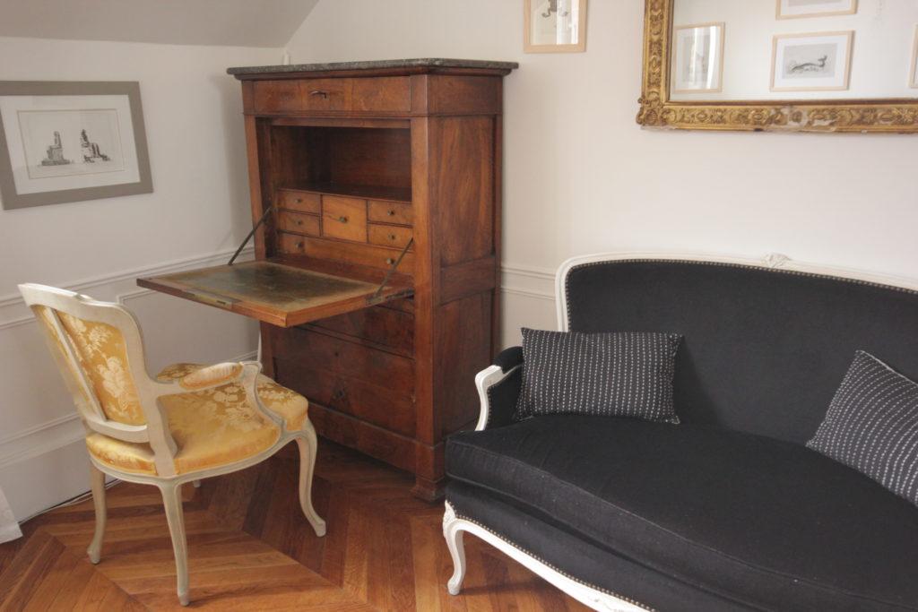 Un appartement 2 pièces complètement rénové et transformé en appartement haussmannien. Mobilier classique chiné, beau secretaire Napoléon compact et fonctionnel