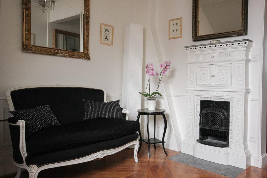 Un appartement 2 pièces complètement rénové et transformé en appartement haussmannien. Décoration classique, salon louis xv chiné et repeint, miroirs à la feuille d'or, gravures anciennes