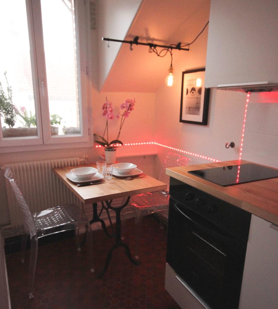 Un appartement 2 pièces complètement rénové et transformé en appartement haussmannien. Coin repas avec guirlande led multicolore pour donner un style tendance et chaleureux